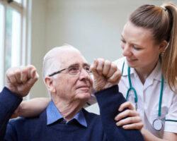 Nurse Assessing Stroke Victim By Raising Arms